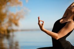Young girl practicing yoga exercise at quiet pier in autumn park.  royalty free stock photos