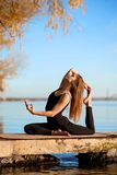 Young girl practicing yoga exercise at quiet pier in autumn park stock photos