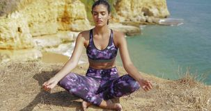 Young girl practicing yoga on shore stock footage