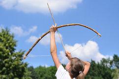 Young girl practising archery. Standing aiming her bow and arrow up into the sky in the countryside Stock Photo