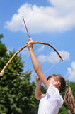 Young girl practising archery. Standing aiming her bow and arrow up into the sky in the countryside Stock Images