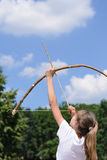 Young girl practising archery. Standing aiming her bow and arrow up into the sky in the countryside Stock Image