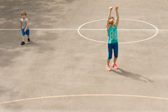 Young girl practising on a basketball court Stock Photos
