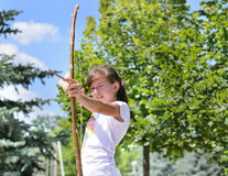 Young girl practising with a bow and arrow. Young girl practising with a homemade bow and arrow carefully taking aim at her target Stock Photos