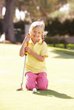 Young Girl Practising Golf. On Putting On Green Royalty Free Stock Photography