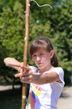Young girl practising her archery. Close up view of a young girl practising her archery taking aim with a homemade bow and arrow in a park Stock Photo