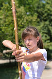 Young girl practising her archery. Close up view of a young girl practising her archery taking aim with a homemade bow and arrow in a park Stock Image