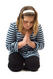 Young Girl Praying. Young girl on her knees praying, isolated against a white background Stock Photo