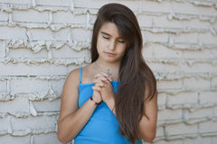 Young girl praying with her hands held toge Stock Photography
