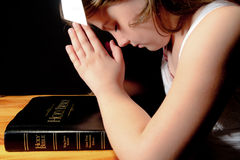 Young Girl Praying Over Bible. Young girl kneeling and praying over bible Royalty Free Stock Photo