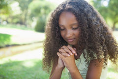 Young girl praying in the park Royalty Free Stock Photography
