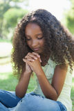 Young girl praying in the park Stock Images