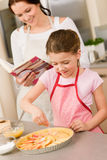 Young girl prepare apple pie with mother Royalty Free Stock Photography