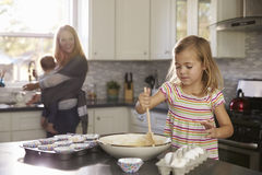 Young girl prepares cake mix, mum and baby in the background Royalty Free Stock Images