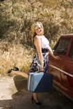 A Young Girl Prepares For A Trip. A young woman prepares to leave on a trip. Antique care and old luggage add to a vintage feel royalty free stock images