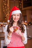 Young Girl preparing for Christmas. And holding hot tea / coffee Royalty Free Stock Photos