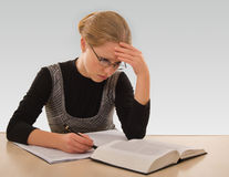 Young girl is preparing for the exam. Young girl with a book to pass the exam stock image