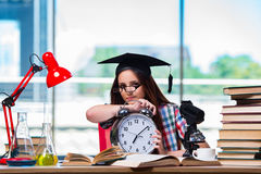 The young girl preparing for exams with large clock Stock Image