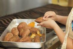 Young girl preparing sweet potatoes Royalty Free Stock Photos