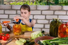 Young girl preparing vegetables for bottling stock image