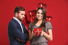 Young girl is presenting a gift and balloons to her resentful handsome man. Valentines day couple gift Royalty Free Stock Images