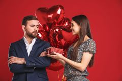 Young girl is presenting a gift and balloons to her resentful handsome man. Valentines day couple gift Royalty Free Stock Photos