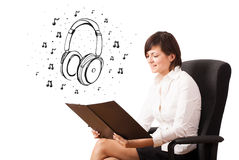 Young girl presenting headphone and musical notes Royalty Free Stock Photo