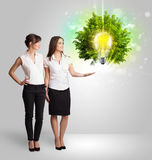 Young girl presenting idea light bulb with green tree Royalty Free Stock Images