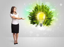 Young girl presenting idea light bulb with green tree Stock Photo