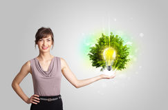 Young girl presenting idea light bulb with green tree Stock Photography