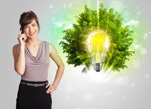 Young girl presenting idea light bulb with green tree Stock Images