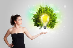 Young girl presenting idea light bulb with green tree Royalty Free Stock Photo