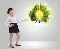 Young girl presenting idea light bulb with green tree Royalty Free Stock Photos