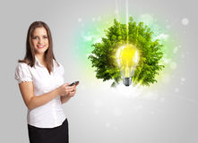 Young girl presenting idea light bulb with green tree Royalty Free Stock Photography