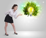 Young girl presenting idea light bulb with green tree Royalty Free Stock Image
