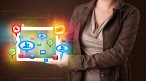 Girl presenting a tablet with colorful social icons and signs Royalty Free Stock Photography