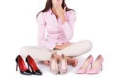 Young girl presents three modern pairs of high-heeled shoes isolated on a white background. Royalty Free Stock Images
