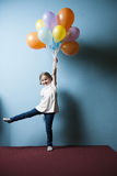 Young girl pretending to be lifted up by bunch of balloons Royalty Free Stock Image