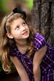 Young girl pretty long blond hair. A young girl with a black bow in her long blond hair, standing by a tree looking upwards. Shallow depth of field Stock Image