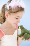 Young girl in princess costume kissing plush frog Royalty Free Stock Photo