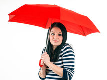 Young girl is protected from bad weather with a red umbrella Royalty Free Stock Photo