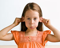 Young girl pulling ears Stock Images