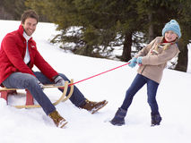 Young Girl Pulling Father Through Snow On Sled. Smiling at camera Royalty Free Stock Photos