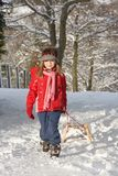 Young Girl Pulling Sledge Through Snowy Landscape Stock Images