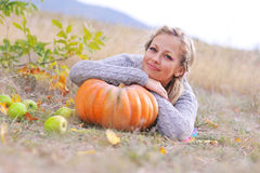 Young girl with pumpkin outdoors. Young beautiful girl lying in the field with pumpkin and apples Royalty Free Stock Photography