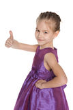 Young girl in the purple dress holds her thumb up Stock Photography