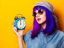 Young girl with purple hair and alarm clock Royalty Free Stock Photos
