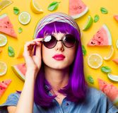 Young girl with purple hair and sunglasses. On spring fruits background royalty free stock image