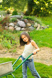 Young girl pushing wheelbarrow in the garden Royalty Free Stock Photo