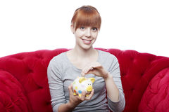 Young girl put coin in piggybank Royalty Free Stock Photos